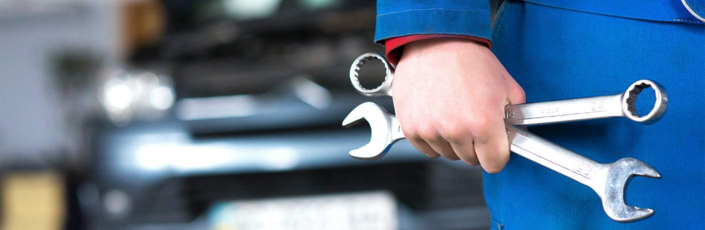 Mechanic Holding Wrenches in Hand