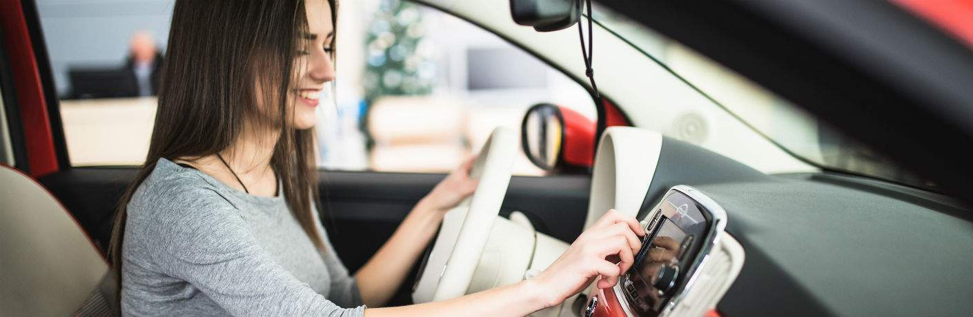smiling brown-haired woman using car stereo in subcompact vehicle