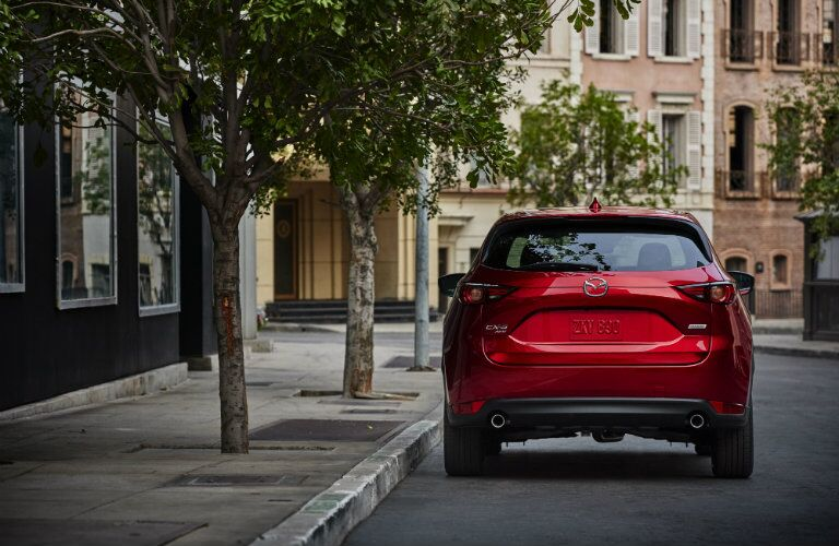 red 2017 Mazda CX-5 parked on street rear angle