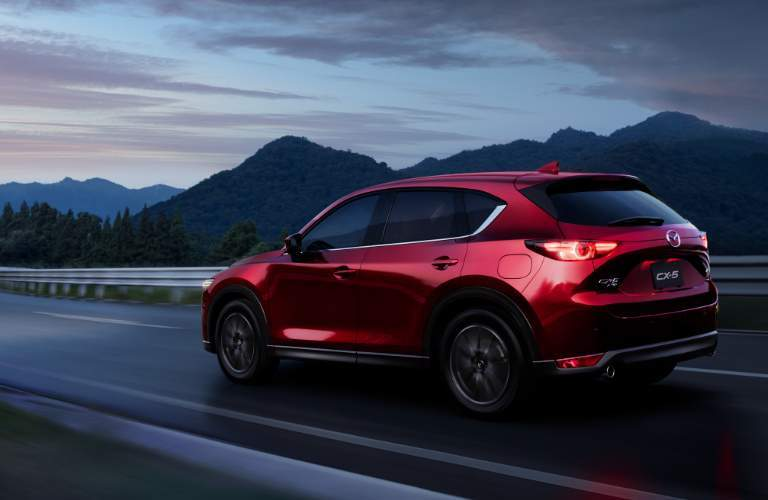 red 2017 Mazda CX-5 driving toward sunset exterior side rear view