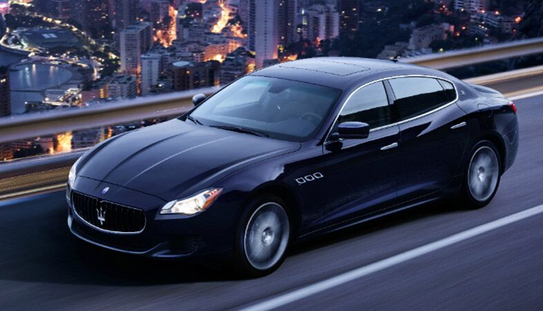 full view of the 2018 maserati quattroporte driving in a city