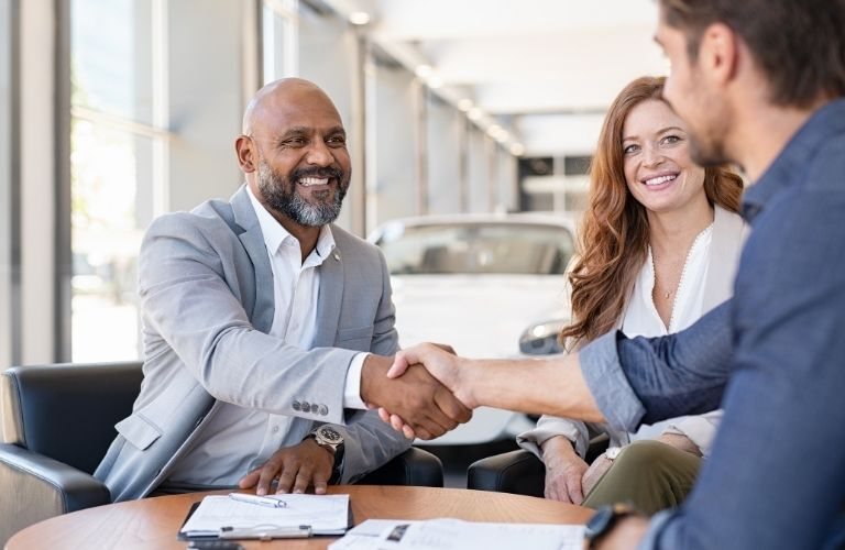 Couple shaking a dealerships agents hand