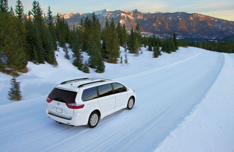 2017 toyota sienna driving through snow all-wheel drive white exterior color