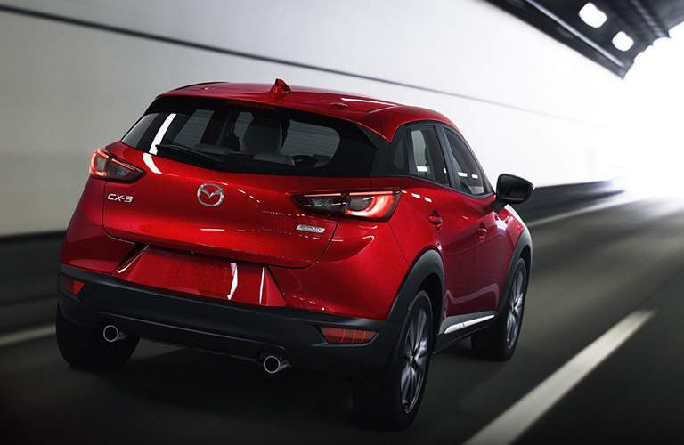 rear shot of red 2018 Mazda CX-3 driving in a tunnel