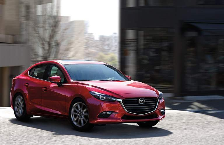 Front quarter profile of the 2018 Mazda3 parked by some buildings on a cobblestone road