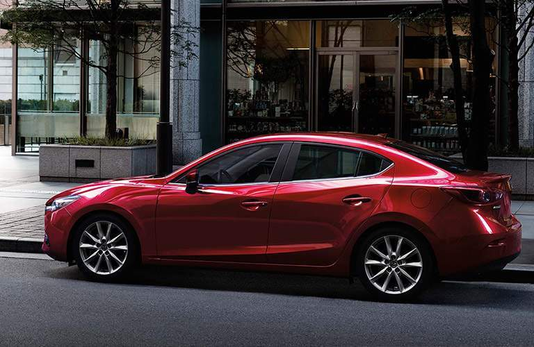 Side profile of the 2018 Mazda3 parked outside of a building with big glass windows