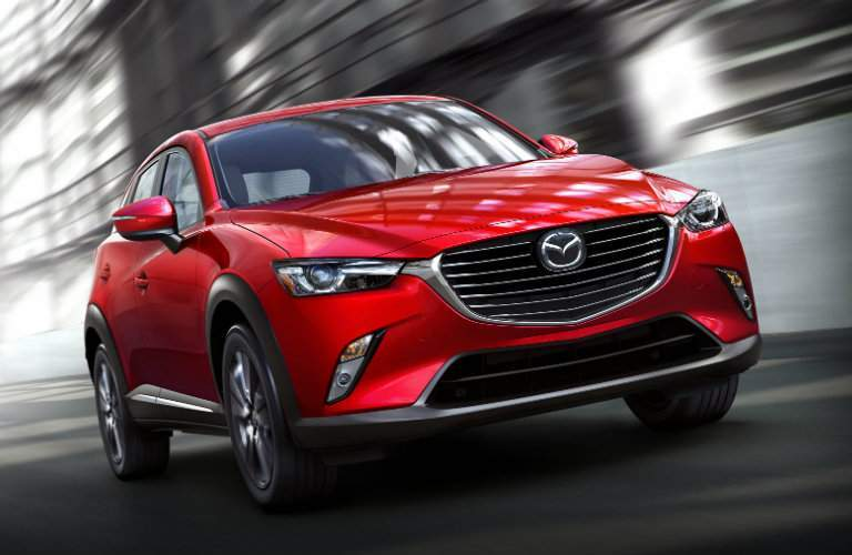 Red 2018 Mazda CX-3 driving with blurred background