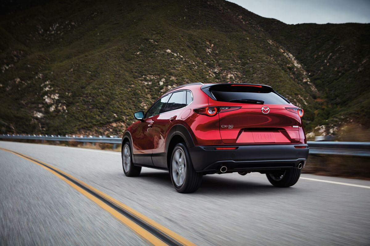Mazda CX-30 driving down a rural highway near Portsmouth, NH