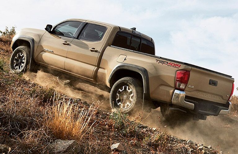 Tan Toyota Tacoma scaling up inclined hill