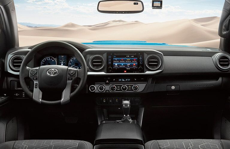 2017 Toyota Tacoma dashboard and steering wheel with view of sand dunes through windshield