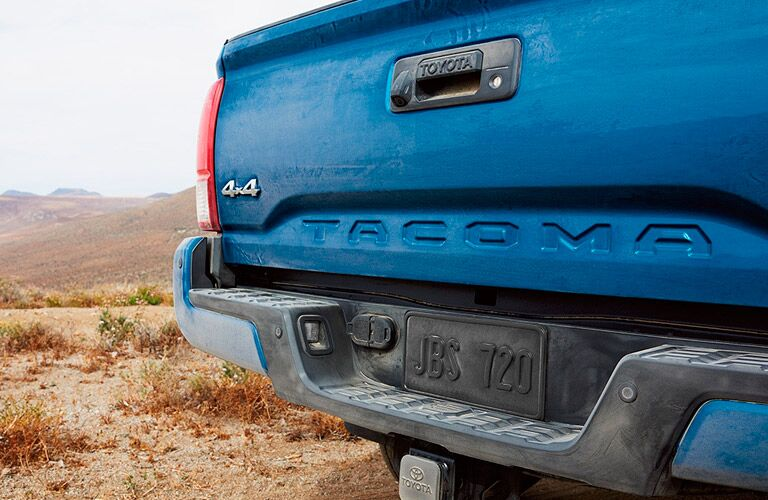 Blue Toyota Tacoma rear shot with tailgate and bumper prominently shown