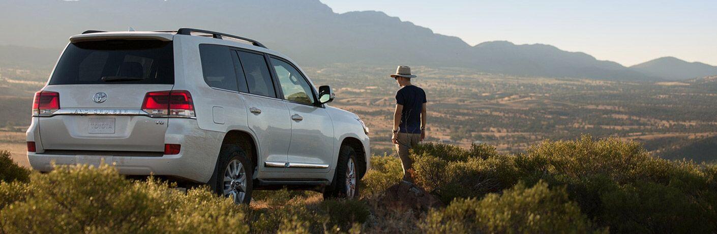 Man walking towards 2018 Toyota Land Cruiser set against safari landscape