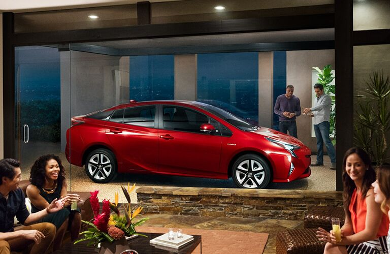 Profile view of red Toyota Prius parked in front of modern building