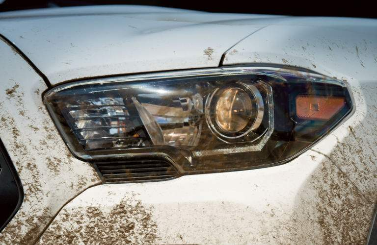 Muddy Toyota Tacoma front panel with headlight shining in daytime