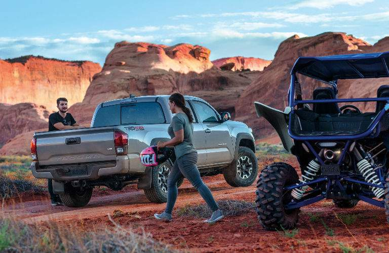 Two people walking towards 2018 Toyota Tacoma in desert landscape with ATV to right of frame
