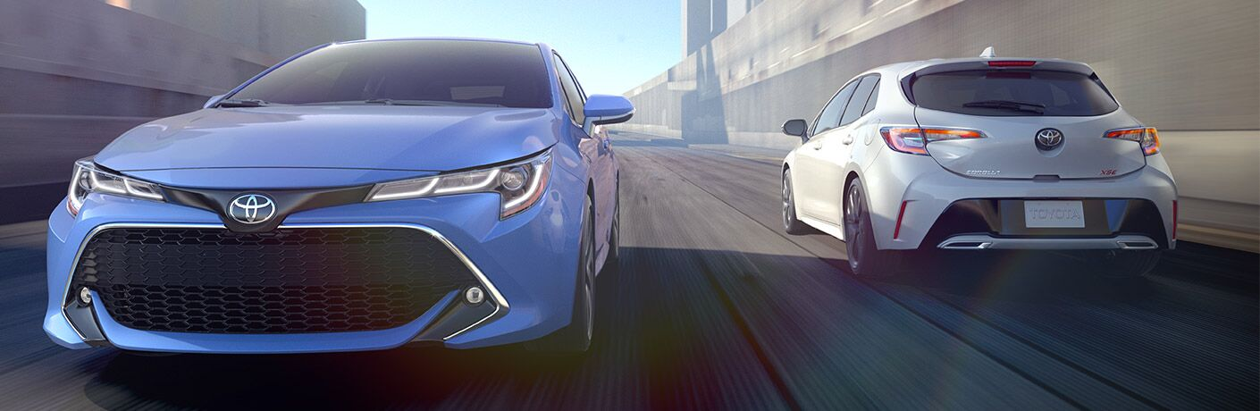 Blue and white 2019 Toyota Corolla Hatchback models driving on city road in daytime