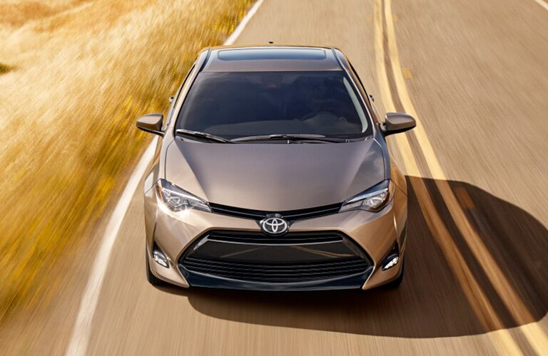 Overhead view of tan 2019 Toyota Corolla driving on country road
