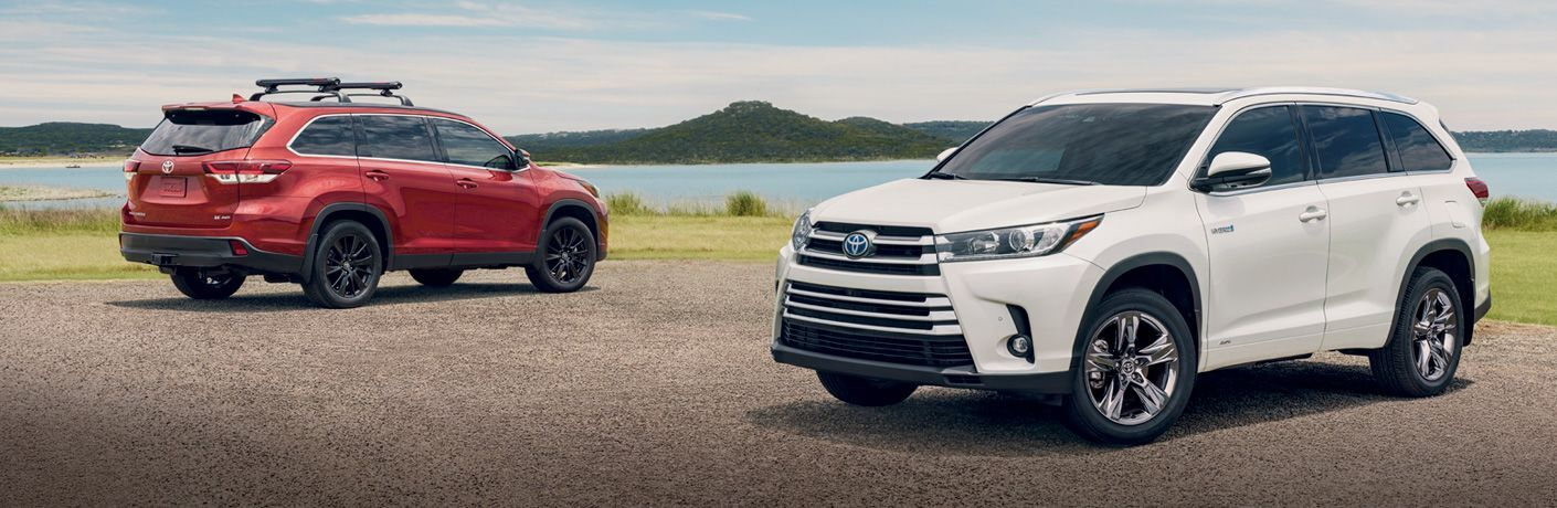 Red and white 2019 Toyota Highlander models parked in driveway next to waterfront