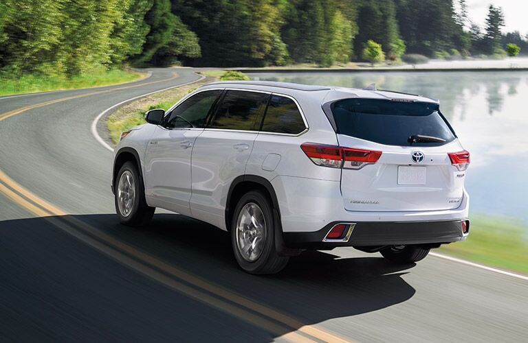 Rear shot of white 2019 Toyota Highlander driving on waterfront road