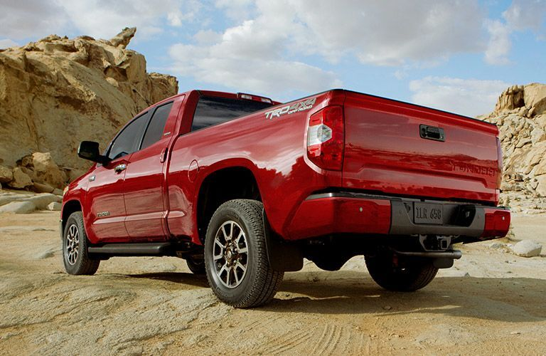 Rear view of red 2019 Toyota Tundra parked next to rocky formations