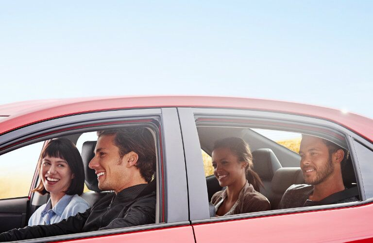 Four people smiling while driving inside 2019 Toyota Corolla