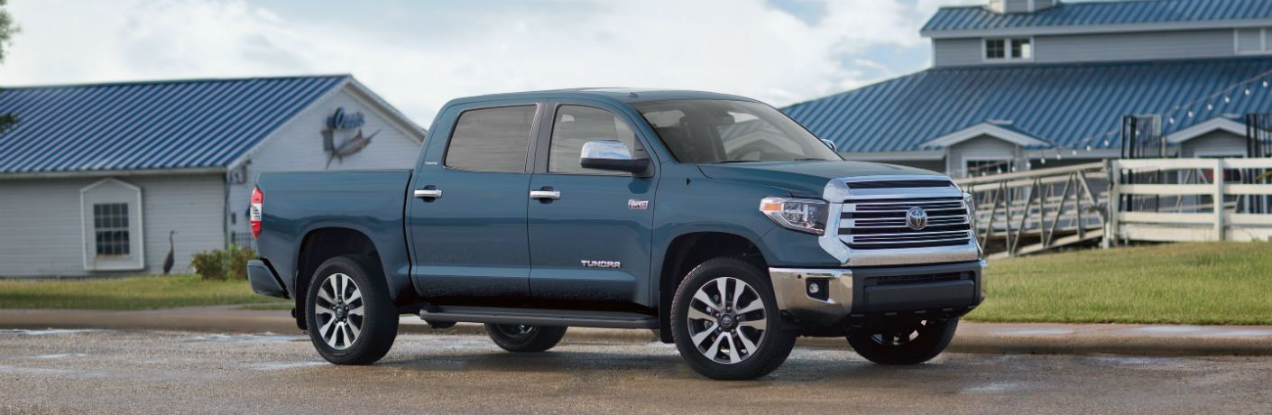 Profile view of blue 2019 Toyota Tundra parked in front of blue-roofed house