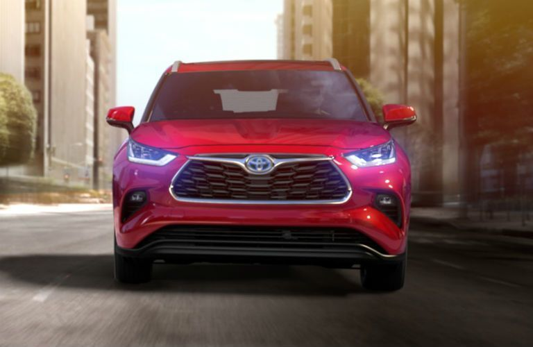 Front view of red 2020 Toyota Highlander with headlights illuminated