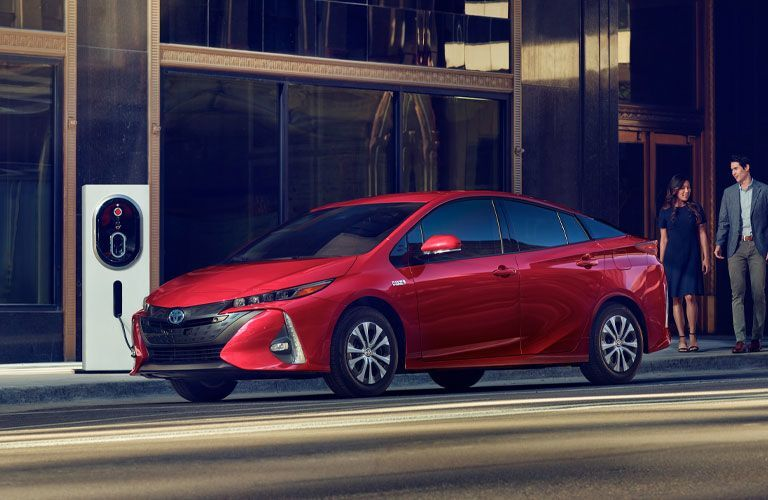 Red 2020 Toyota Prius Prime parked in front of electric charger
