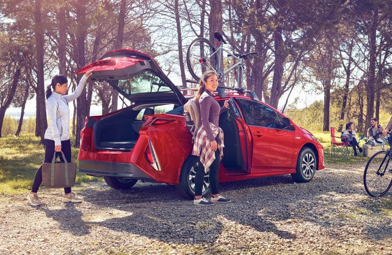 Two women standing on either side of 2020 Toyota Prius Prime