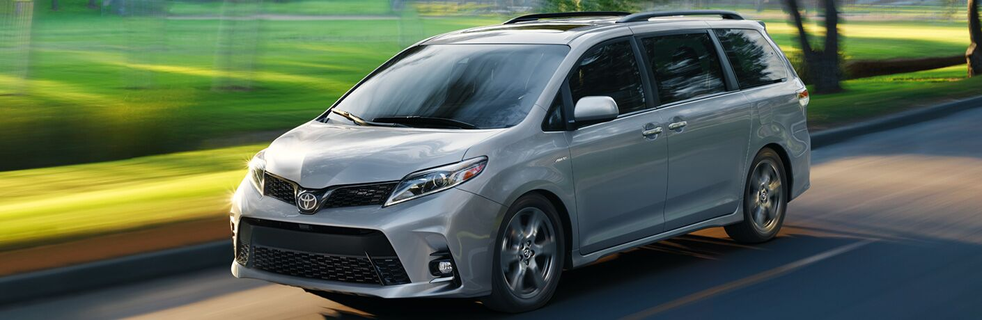 Silver 2020 Toyota Sienna driving on residential country road