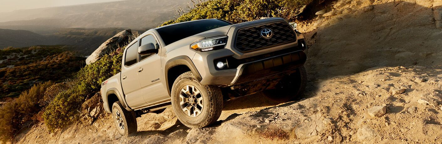 Exterior view of a tan 2020 Toyota Tacoma driving up a rocky hillside