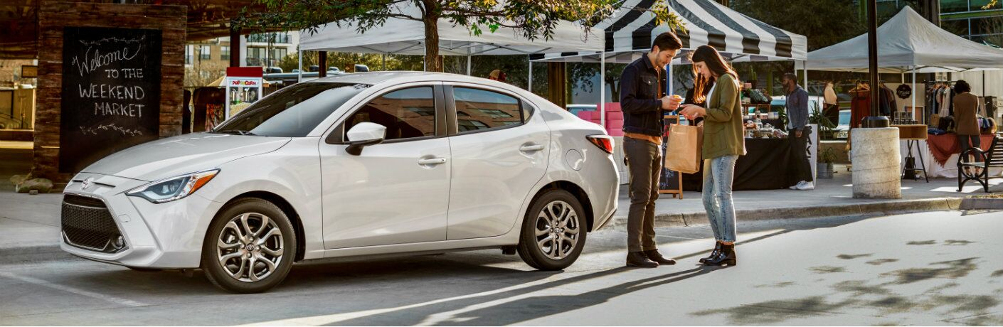 Two people standing next to white 2019 Toyota Yaris parked near marketplace