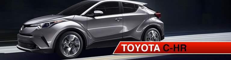 Gray Toyota C-HR driving down dark road with lights illuminating