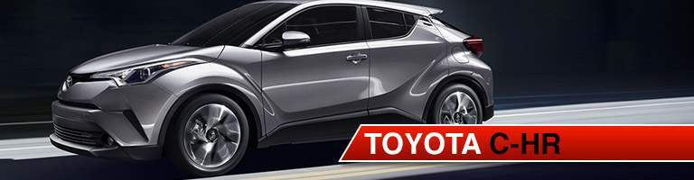Silver Toyota C-HR speeding down dark and empty road