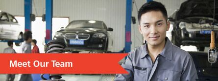 Meet Our Team banner over image of mechanic in a shop with cars