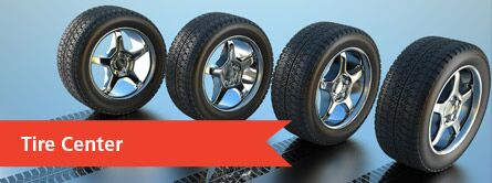 Four tires in a row with the words Tire Center at the bottom