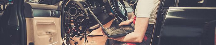 Mechanic sitting in vehicle and holding laptop