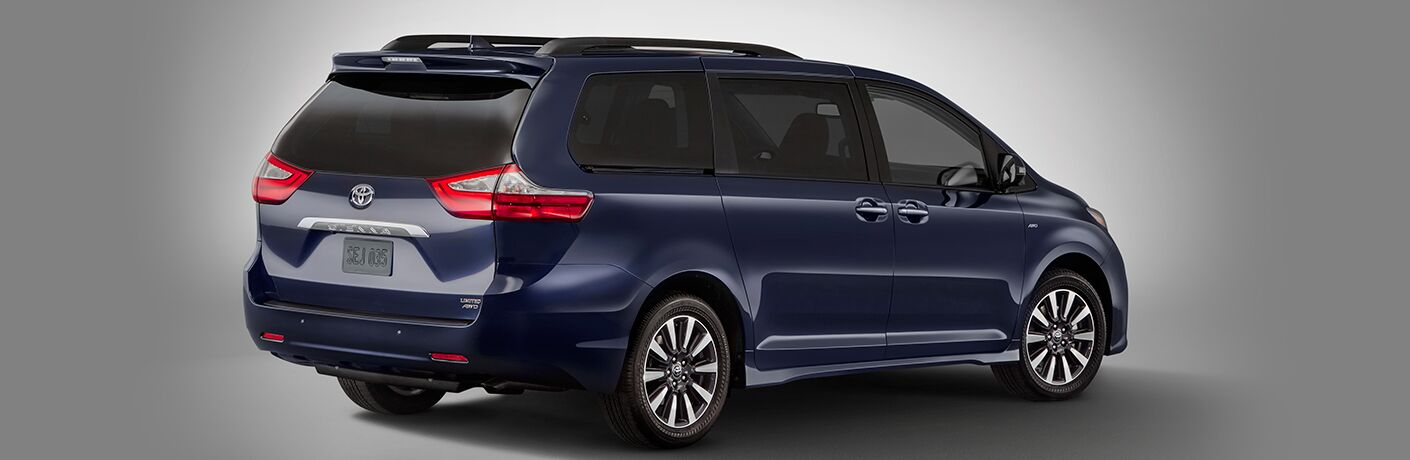 Rear profile view of blue 2018 Toyota Sienna on silver background