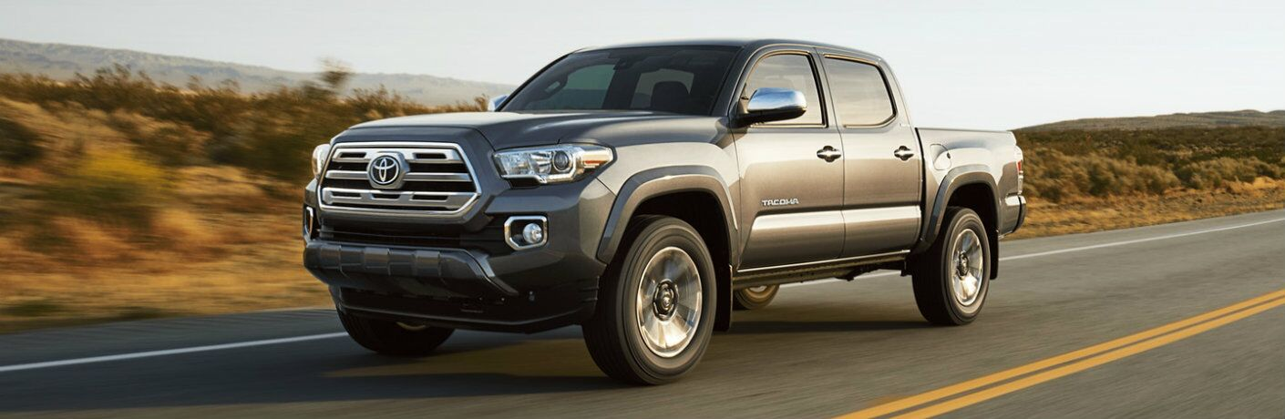 Profile view of gray 2018 Toyota Tacoma driving down desert road at sundown