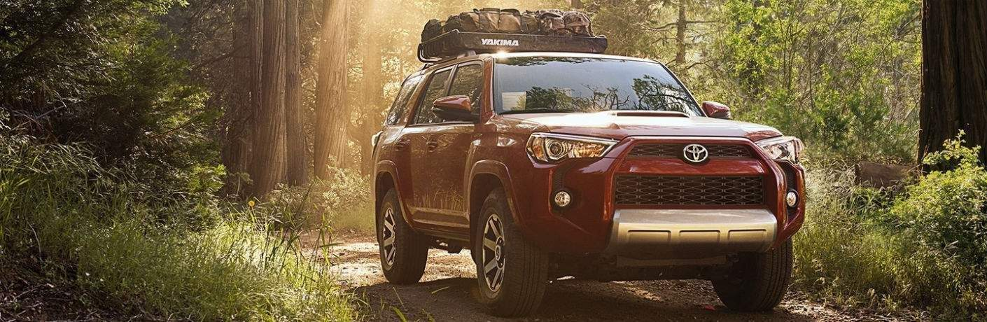 Red 2018 Toyota 4Runner driving through wooded terrain while carrying cargo on top