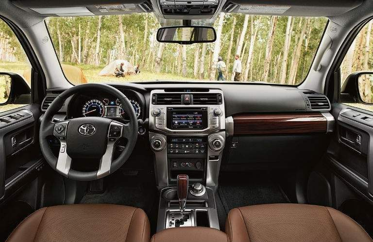 Front dashboard and seats of 2018 Toyota 4Runner with gear shifter and steering wheel prominent