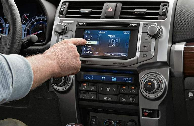 Man using finger to control Toyota Entune infotainment interface