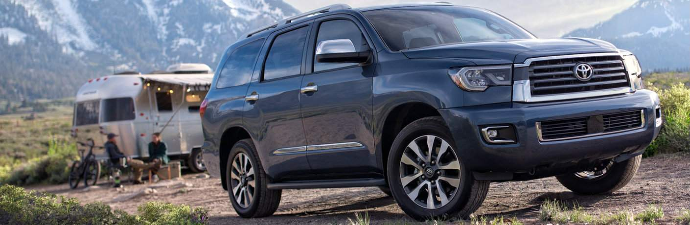Blue-Grey 2018 Toyota Sequoia Parked in Front of a Camping Trailer