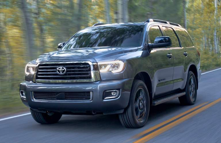 Blue-Grey 2018 Toyota Sequoia Driving by a Forest
