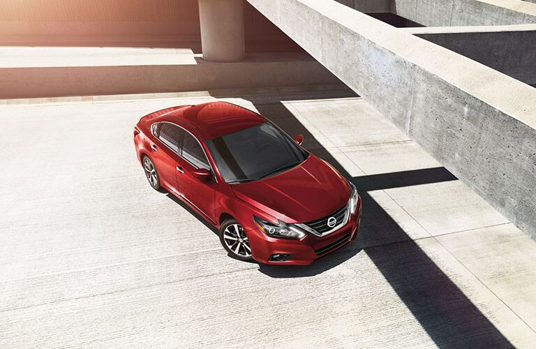 Red Nissan Altima parked under concrete structure in sunlight