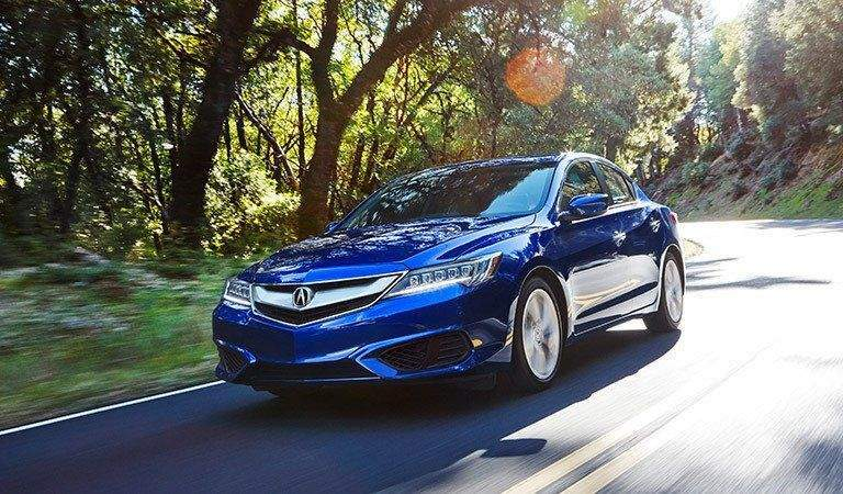 full view of the Acura ILX driving on a forest road