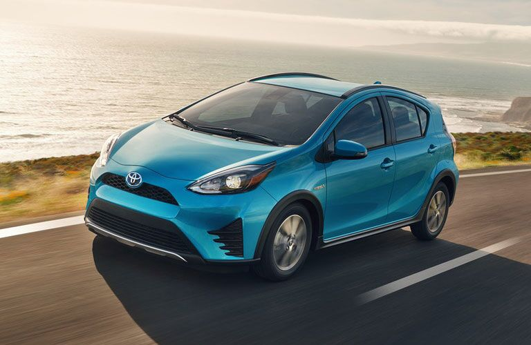 Toyota Prius c driving by some water