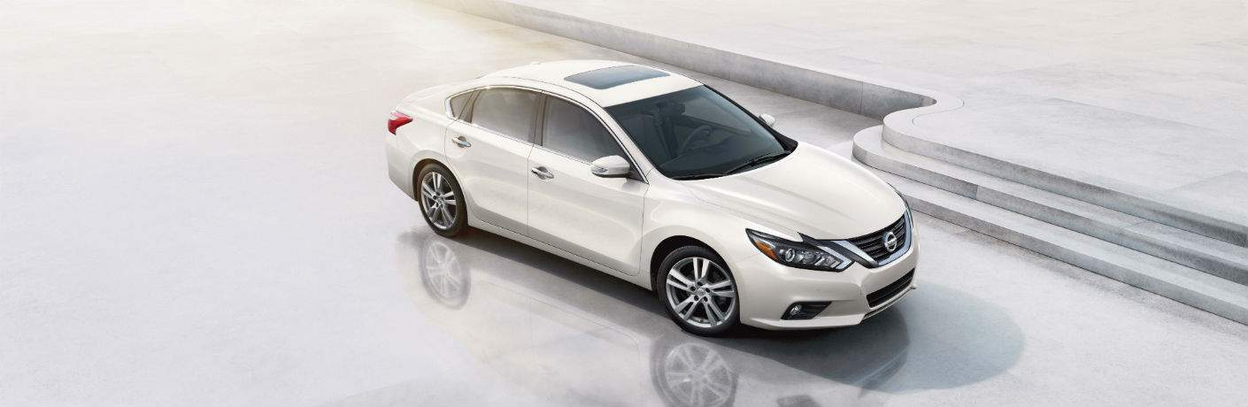 High shot of white 2018 Nissan Altima parked next to steps