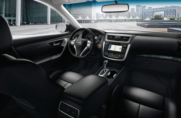 Front two seats of 2018 Nissan Altima with steering wheel and infotainment system prominently shown
