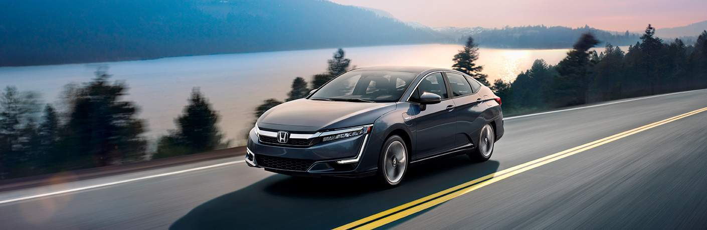 2018 Honda Clarity Plug-In Hybrid driving on a road overlooking a lake at sunset